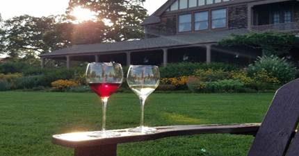 Image of two wine glasses on an adirondack chair on the Great Lawn