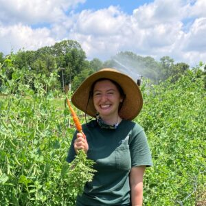 Farm manager Dana smiling and holding a carrot